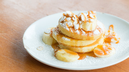 bannana: Bannana pancake with caramel and powdered sugar on wooden table.