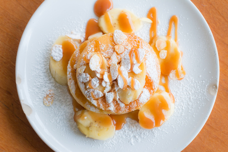 cakes background: Bannana pancake on wooden table from above. Stock Photo