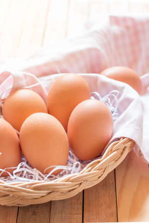 ligh: Eggs in a basket on wooden table with ligh from behide.