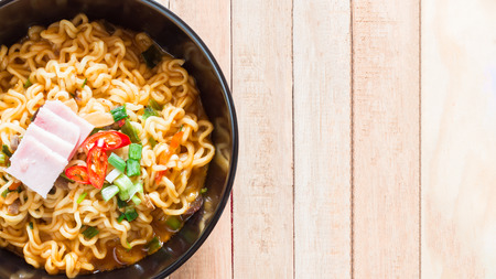 Top view of korean noodles(Ramyun) in black bowl on wooden table. Stock Photo