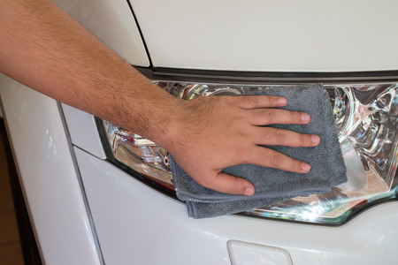 dry cleaners: Cleaning car with microfiber cloth by a mans hand.