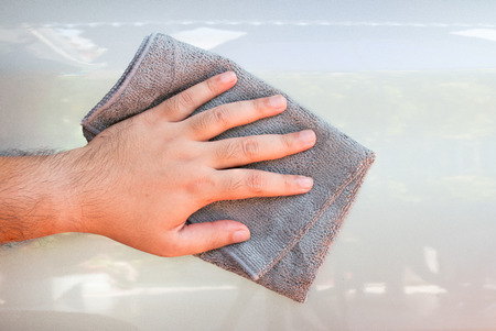 valeting: Cleaning car with microfiber cloth by a mans hand.