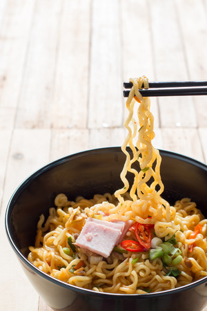 ramen: Korean noodles(Ramyun) in black bowl on wooden table and chopstick.
