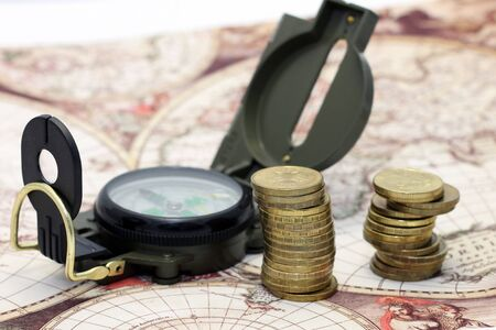 Money and compass lie on the background of the map of the world photo