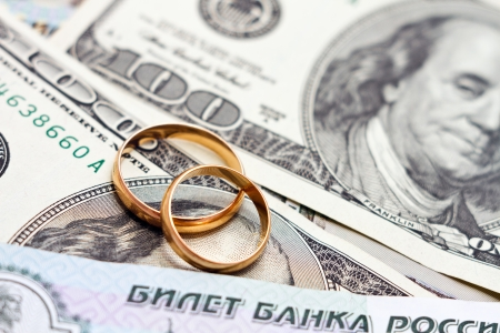 Wedding rings, gold chain and earrings in the form of hearts lie on money
