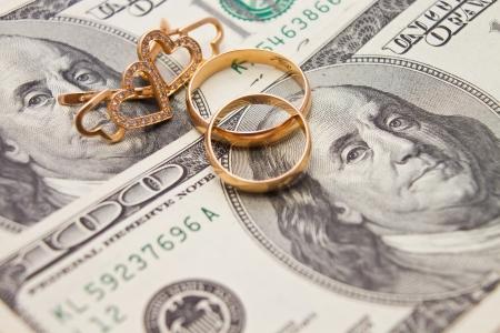 Los anillos de boda, la cadena de oro y aretes en forma de corazón se encuentran en el dinero Foto de archivo - 21066266