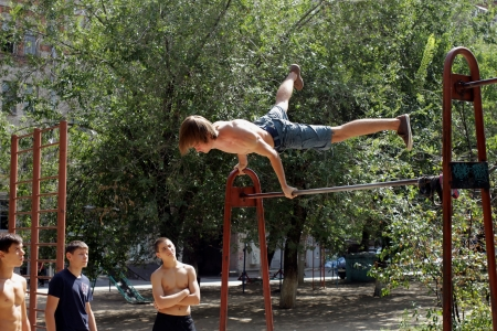 on the skids: VOLGOGRAD - AUGUST 19  Young people perform acrobatics on the bar under the open sky  August 12, 2012 in Volgograd, Russia