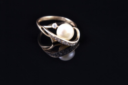 reflectivity: gold ring with a pearl is reflected from the floor
