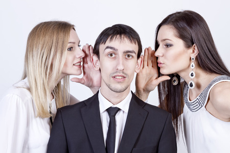 puzzlement: Two girls whispering guy in his ears Stock Photo