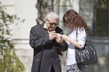 VOLGOGRAD - APRIL 25 Young woman helps the veteran to understand the new cell phone   April 25, 2014 in Volgograd, Russia   Editorial