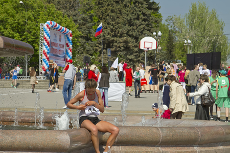 volgograd: Participant of the Volgograd marathon takes plate number with t-shirts sitting at the fountain of Arts