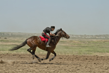 SMALL CHAPURNIKI, VOLGOGRAD, RUSSIA - MAY 24 TRider dressed in Cossack uniform participates in a brown horse devoted to celebration of the Sabantuy   May 24, 2014 in Volgograd, Russia
