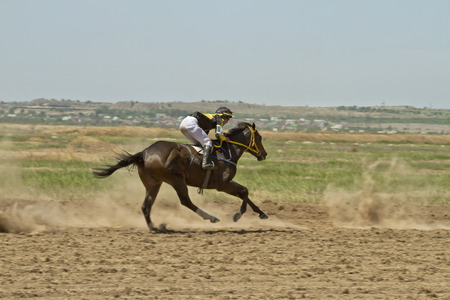 SMALL CHAPURNIKI, VOLGOGRAD, RUSSIA - MAY 24 The jockey riding a horse during the horse races devoted to celebration of the Sabantuy   May 24, 2014 in Volgograd, Russia