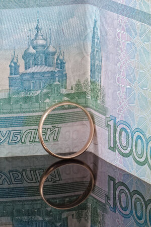 reflectivity: Golden wedding ring on the background of banknotes thousand rubles on a reflective surface Stock Photo