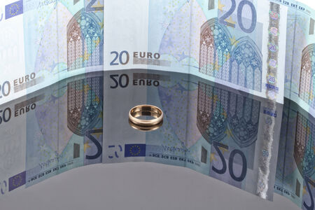 reflectivity: Gold wedding ring on the background of Euro banknotes with reflection