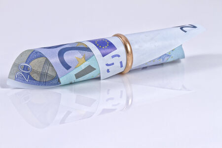 Banknote of 20 Euro collapsed in a gold wedding ring