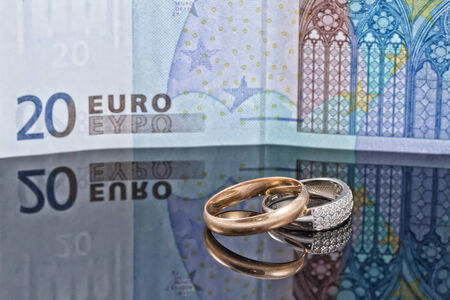 reflectivity: Gold and silver wedding rings on background of 20 Euro banknote Stock Photo