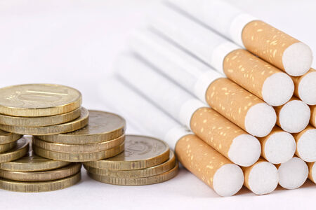 Pyramid of gold coins and cigarettes are composed of a pyramid  photo