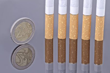 Cigarette and the 2 Euro coin on a reflective surface photo