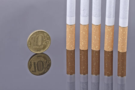 reflectivity: Cigarette and ten rouble coin on a reflective surface