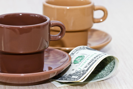 tipping: Sketch   tips in dollars in the cafe  A bit of cash lying under an empty coffee Cup