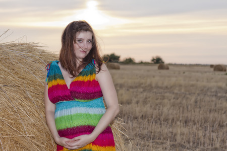 pacification: Portrait of a young pregnant woman at the haystack