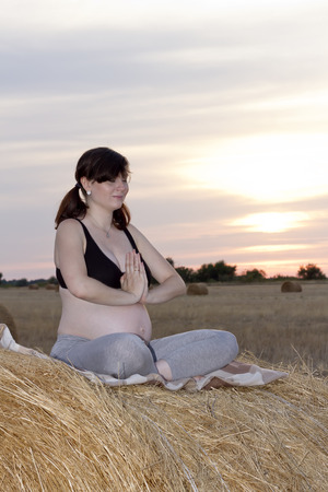 haymow: Beautiful pregnant woman practicing yoga sitting on a haystack at sunset Stock Photo