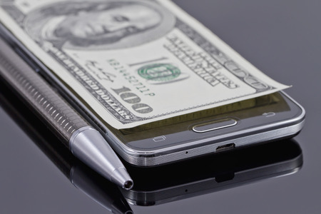 reflectance: new smartphone, ballpoint pen and hundred dollars lying on a black reflective surface