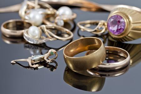 Anillos de oro, aretes y cadenas en una superficie reflectante Foto de archivo - 35120946