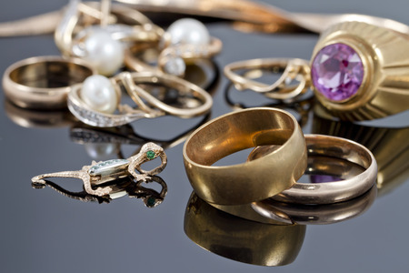 reflectance: gold wedding rings, earrings and chains on a reflective surface