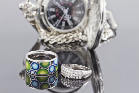 silver ring with precious stones and a ring with a colored ceramic enamel on the background of pocket watches Imagens