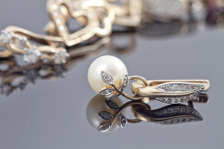 embellished: set of decorative gold earrings with ring embellished with pearls on the reflecting surface