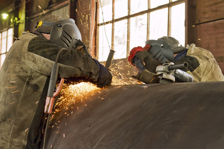 skilled labour: two welders are parallel to the welding of the shell of the heat exchanger of large diameter