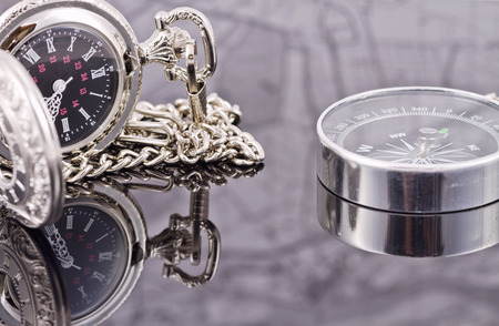 reflectivity: pocket watch and compass lying on the reflecting surface