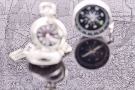 reflectivity: compass and a silver pocket watch on the background reflection maps