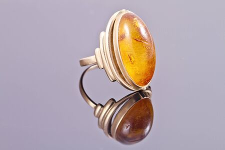 inset: Old gold ring with inset amber on the reflecting surface Stock Photo