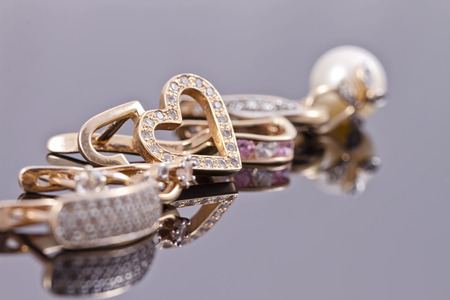 variety of gold earrings with various inserts lie in a line on the reflecting surface Archivio Fotografico