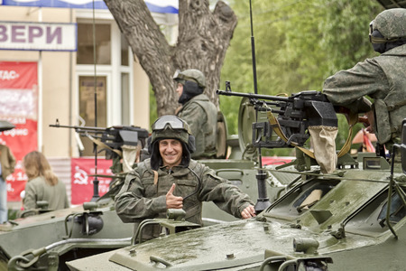 VOLGOGRAD - MAY 9: Happy Russian soldier in the background of a column of armored vehicles built for the victory parade. May 9, 2015 in Volgograd, Russia. Stock Photo - 40096627