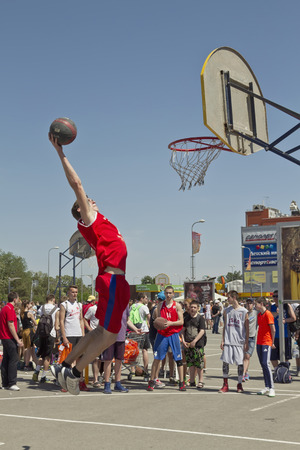 dunk: VOLGOGRAD RUSSIA MAY 24: A young basketball player performs a throw to the slam dunk contest. Annual streetball party organized Europa city Mall on May 24 2015 in Volgograd Russia. Editorial