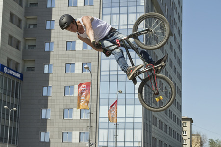 bmx bike: VOLGOGRAD - MAY 24: Young guy in jeans and a t-shirt on a BMX bike performs stunt soaring high in the air. May 24, 2015 in Volgograd, Russia.