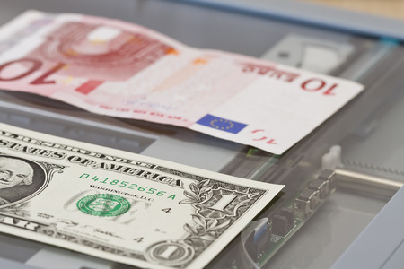 Denominations of one dollar and ten euros lie on the copy machine photo