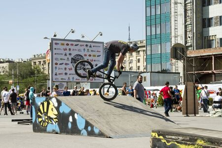 bmx bike: VOLGOGRAD - MAY 24: The athlete is an extreme sports enthusiast performs a trick on a BMX bike with a rotation on the front wheel. The fifth annual competition for the Cup of Europe city Mall . May 24, 2015 in Volgograd, Russia.
