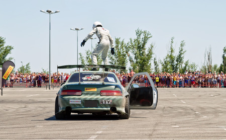 slew: VOLGOGRAD - JUNE 6: Pilot drift team X-Round performs risky stunt climbs to the roof of the car while driving. June 6, 2015 in Volgograd, Russia. Editorial