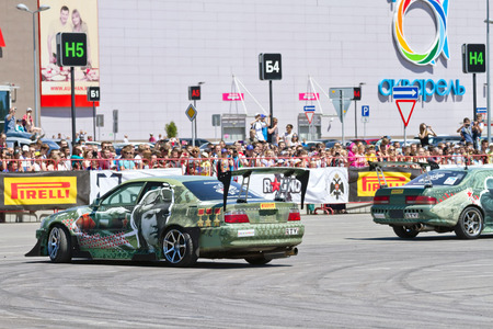 slew: VOLGOGRAD JUNE 6: Drift cars team XRound enters the bend with slip during demonstrations as part of the tour on cities of Russia