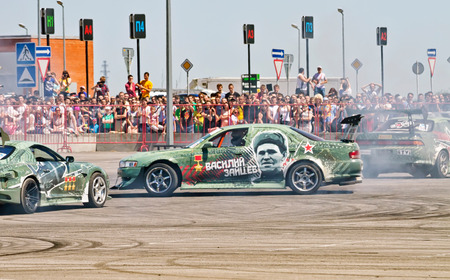 slew: VOLGOGRAD - JUNE 6: Drift cars team X-Round enters the bend with slip during demonstrations as part of the tour on cities of Russia Thank you for the victory!. June 6, 2015 in Volgograd, Russia.