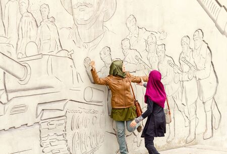 feats: VOLGOGRAD - SEPTEMBER 28:Tourists from Asia pose in front of figures describing feats of Russian soldiers on the walls of Mamayev Kurgan. September 28, 2014 in Volgograd, Russia. Editorial