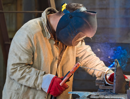 welds: A worker welds a sample to confirm their skills