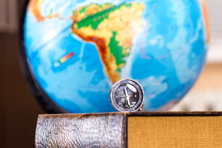 world ideas: The compass lies on an old book, in the background you can see the globe Stock Photo