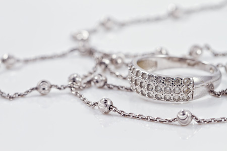 Silver ring with precious stones lie together with a silver chain on acrylic Archivio Fotografico