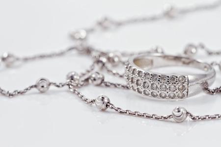 Anillo de plata con piedras preciosas se encuentran junto con una cadena de plata de acrílico Foto de archivo - 44106518